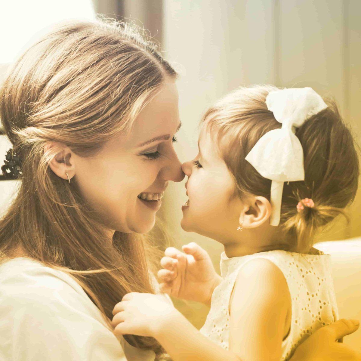 Mutter und Tochter reiben ihre Nasen aneinander